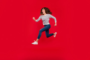 Full length size body photo of fly high charming she her girl quickly running to store shopping mall selling wearing white casual striped sweater denim jeans on red vivid bright background