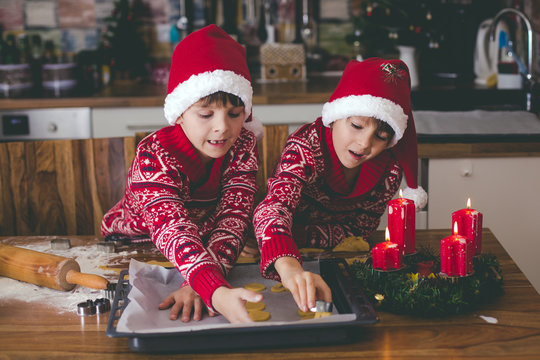 Sweet toddler child and his older brother, boys, helping mommy preparing Christmas cookies at home .
