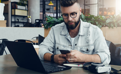 Bearded hipster man in glasses sits in cafe at table, works on laptop, uses smartphone. On table is notebook, camera.