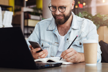 Young bearded man trendy glasses sits cafe in front of laptop computer, uses smartphone, takes notes in notebook.