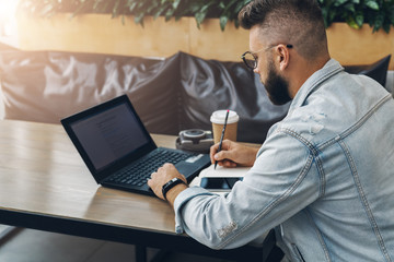 Hipster businessman sitting indoors,writing notes in notepad and working on laptop for solving working issues. Education