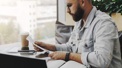 Young attractive bearded hipster man sits in cafe in front of aptop, reading paper documents. Freelancer works remotely.