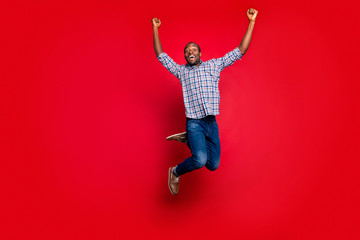 Full length body size portrait of nice funny glad handsome cheerful optimistic positive guy wearing checkered shirt raising hands up party in air isolated on bright vivid shine red background