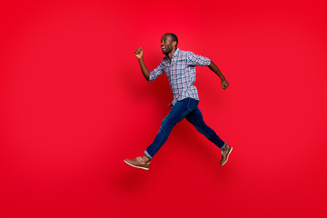 Full length body size profile side view of nice cute handsome attractive cheerful positive sportive guy wearing checkered shirt running in air to goal isolated on bright vivid shine red background