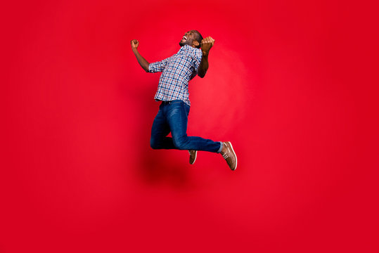 Full length body size portrait of nice funny glad handsome cheerful positive trendy guy wearing checkered shirt showing winning gesture cool party in air isolated on bright vivid shine red background