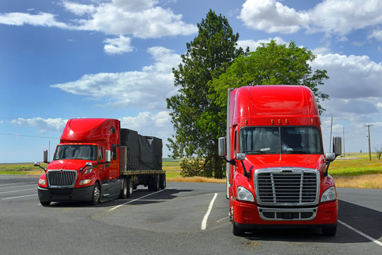 Two big red semi truck on parking
