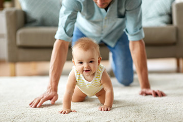 family, fatherhood and parenthood concept - happy little baby girl with father at home crawling on floor