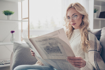 Portrait of nice adorable attractive intelligent wavy-haired lady housewife wearing sweater holding in hands reading interesting digest in light interior room