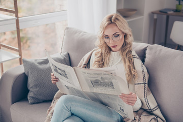 Portrait of nice stylish trendy attractive intelligent wavy-haired lady wife housewife wearing sweater holding in hands reading interesting stories in light interior room