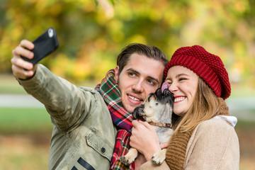 Frau und Mann mit Hund beim Herbst Spaziergang nehmen ein Selfie mit dem Handy auf, Hund schleckt ins Gesicht