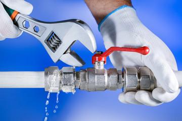 Hands plumber at work in a bathroom, plumbing repair service. Leak of water. Repair plumbing.