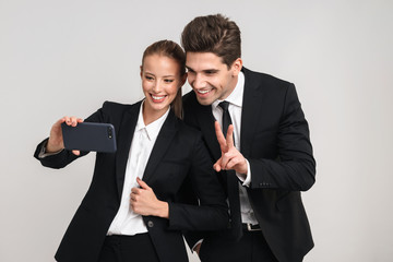 Portrait of a happy young business couple wearing suits