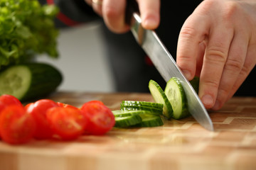 Cook holds knife in hand and cuts on