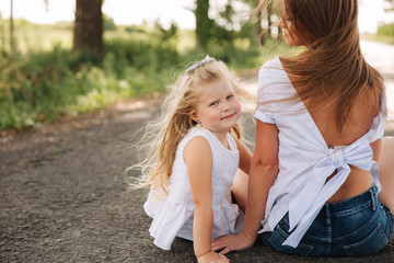 Attractive Mom and blonde hair daughter sits on road near big alley. They smile and look to natune. Front view