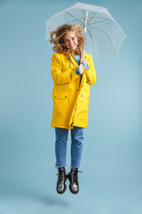 Full length image of positive woman 20s wearing yellow raincoat standing under transparent umbrella, isolated over blue background