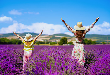 mother and daughter in lavender field rejoicing