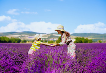 mother and daughter at lavender field stand holding hands