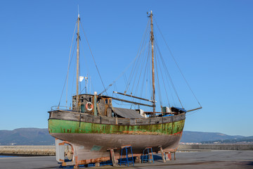 old wooden fishing boat on the shore to dry