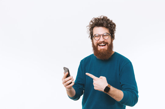 Cheerful handsome bearded man poinitng at smart phone