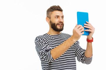 Joyful emotional man taking photo on his tablet