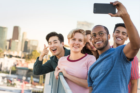 Group of friends taking selfie with city skyline in background