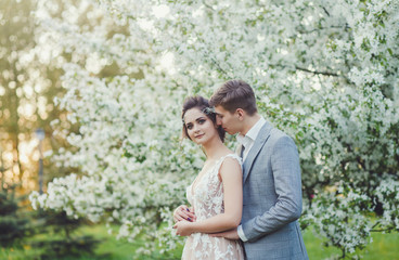 Bride and groom in a park kissing. Couple newlyweds in blossom garden