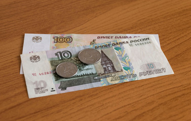 117 rubles on wooden background. russian coins and bills for backgrounds and illustrations of financial and economic news