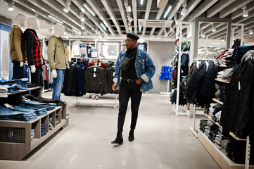 Stylish casual african american man at jeans jacket and black beret with fanny pack or waist bag walking at clothes store.