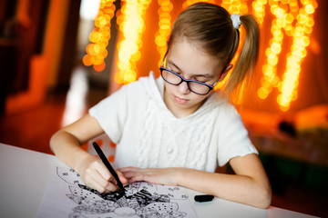 Blonde girl in the white knitting dress and big black glasses drawing santa claus. Christmas and New Year theme, yellow bokeh