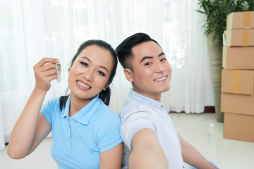 Young Asian woman and man with key of new real estate smiling at camera taking selfie at home