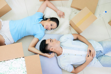 From above shot of cheerful Asian couple in love lying on floor among carton boxes while moving