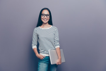 Portrait of nice confident attractive lovely cheerful straight-haired lady wearing striped pullover holding in hand laptop isolated over gray pastel background