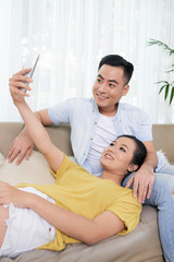 Cheerful young Asian couple sitting on couch at home and taking selfie with phone together