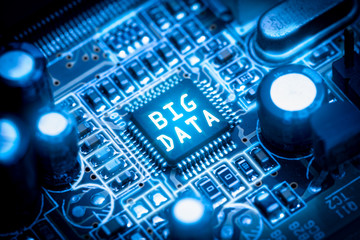The abstract image of the chipset illumination on the computer mainboard overlay with ''big data'' text. The concept of big data, hardware, futuristic, information and technology.