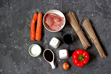 Ingredients for cooking buckwheat soba noodles with pork and vegetables: dry buckwheat soba noodles, sweet red pepper, pork, oyster sauce, soy sauce, sugar, salt, pepper, carrots, onion.