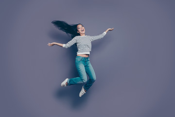 Full length body size view of lovely attractive cheerful positive optimistic girl wearing striped pullover jeans denim having fun rejoicing in air isolated over violet purple pastel background