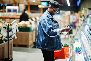 Stylish casual african american man at jeans jacket and black beret holding basket and milk at hand, standing near fridge and shopping at supermarket.
