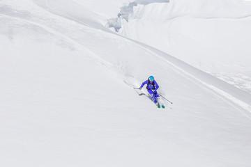 one freerider skiing downhill in fresh powder snow