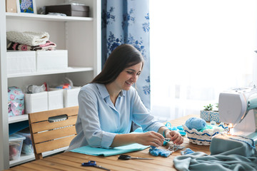 woman with long dark hair sews on sewing machine