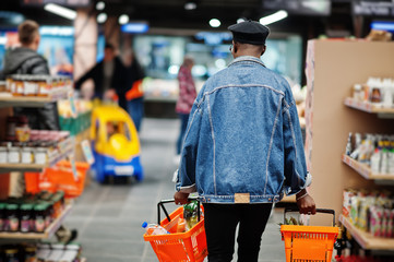 Back of stylish casual african american man at jeans jacket and black beret holding two baskets, walking and shopping at supermarket.