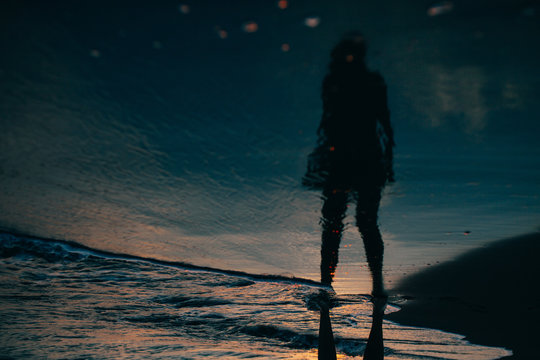 Reflection in the sea water of a young woman standing and looking to the sea