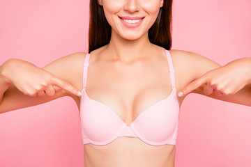 Cropped close up portrait of glad slim lovely with result her she girl showing fingers to perfect cleavage in pale pink bra isolated on pink background wellbeing concept
