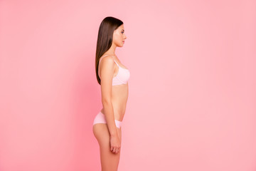 Vertical photo of cute thin young she her girl woman standing staring in empty space wearing pale pink underwear isolated on rose background