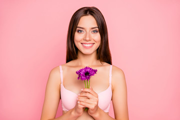 Close-up portrait of nice cute sweet lovely attractive charming cheerful girl in beige bra holding in hands violet flowers dream isolated over pink pastel background