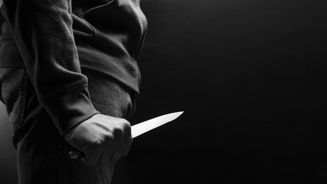 The criminal with a knife weapon threatens to kill. With space for an inscription. News staties, newspaper, social issues, the increase in severity