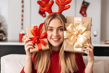 Portrait of gorgeous girl 20s sitting on sofa in living room with gift boxes, while celebrating Christmas