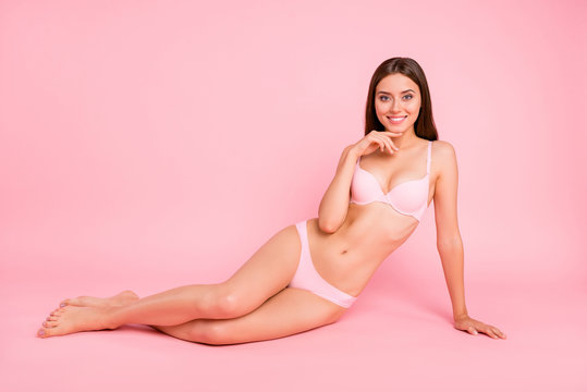 Full length body size photo of attractive young lovely she her lady girlish sitting on floor touching chin demonstrating forms of body on  camera in pale pink bra isolated on rose background