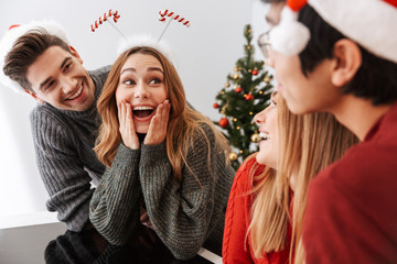 Group of joyous multiethnic people men and women laughing, while celebrating New Year at home
