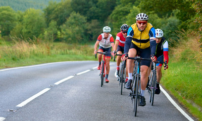 A group of cyclists on a bike race on a country roads in the UK.