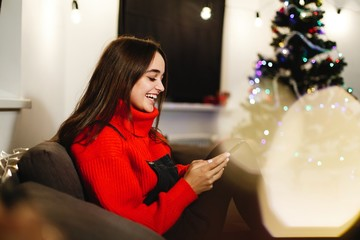 Christmas and New Year vibes. Home decorations. Charming young woman in red sweater sits on the couch before shiny Christmas tree and works with her smartphone